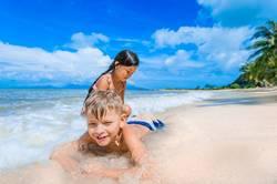 Cute kids having fun on the sunny tropical beach.