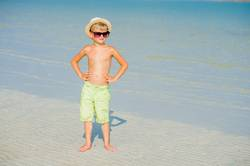 Portrait of a handsome boy on the desert sunny beach