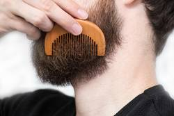 Closeup of a young man styling his long beard with a comb