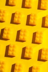 Yellow unicolour plastic geometric cubes. Construction toys