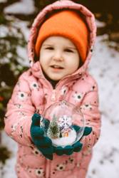 Child hold transparent glass ball with christmas tree