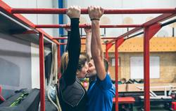 Athletes kissing exercising on monkey bars