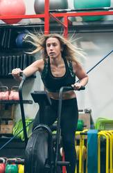 Sportswoman doing air bike at the gym