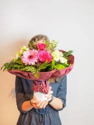 Junge Frau mit Blumenstrauß vor dem Gesicht