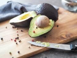 Avocado mit Kern auf einem Holzbrett