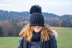 Junge Frau mit einer blauen Mütze über dem Gesicht