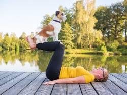 Junge Frau beim Joga mit Hund