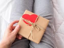 Frau mit Geschenkpaket mit Herz