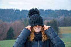 Jungesl ächendes Mädchen mit einer blauen Mütze über dem Gesicht