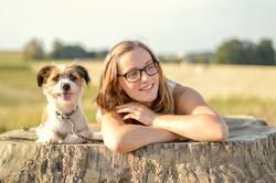 Junge Frau mit enem Hund auf einem Baumstamm