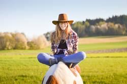 Junge Frau im Schneidersitz auf einem Pferd