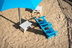 Zwei türkisfarbene Stühle mit türkisfarbenem Sonnenschirm