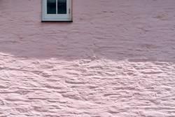 Rosa Haus mit weißem Fenster im Schatten