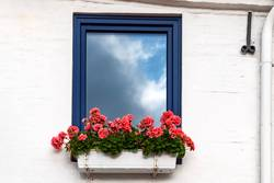 Sonne und Wolken, Fenster, Reflektion und Geranien = Sommer