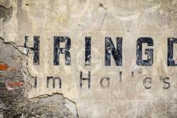 Stück einer alten Wand mit historischen Schriftzügen