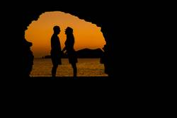 silhouette of young couple loving at the beach at sunset