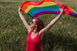 Woman holding the Gay Rainbow Flag on green meadow outdoor