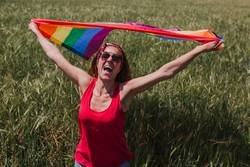 Woman holding the Gay Rainbow Flag on a green meadow outdoors
