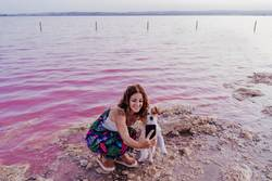 young beautiful woman standing by a pink lake with dog