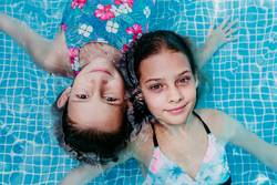 two beautiful teenager girls floating in a pool
