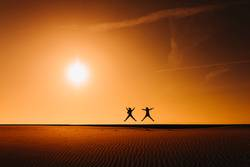 silhouette of two women friends jumping at the beach at sunset