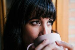 young woman at home by the window having a coffee
