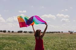 Woman holding the Gay Rainbow Flag on green meadow outdoors