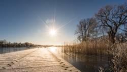 Sonnenflare über einen Steg im See