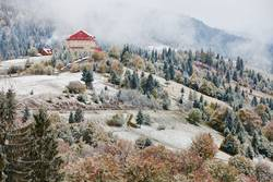 First snow in autumn. Snowfall in mountains. Snow and fog