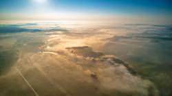 Aerial view of morning foggy sunrise and rural fields