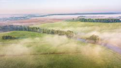 Morning fog over river, meadow and forest. Nature sunlight scene