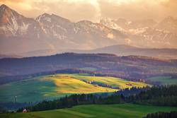 Snow caped mountains and green fields and meadows