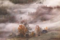 Bergdorf. Wolken aus Nebel und Rauch. Herbstmorgen