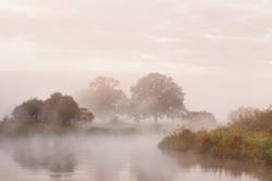 Misty autumn morning on river.