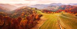 Autumn mountain panorama. Dirt road on top of hills.