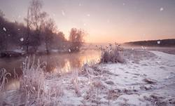 Winter misty dawn on the river. Snowflakes, snowfall