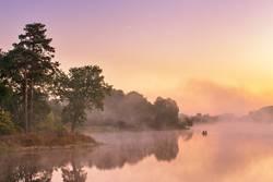 Nebelhafter Morgen auf dem See. Fischerboot an einem nebeligen Fluss