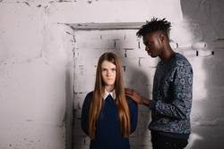 angry girl and caring African student