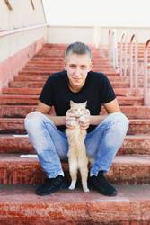 young man holds cat