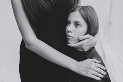 thin hands of an adult woman hugging a young girl
