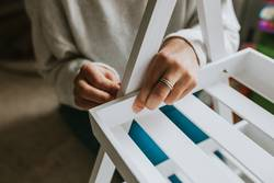 Woman assembling furniture at home