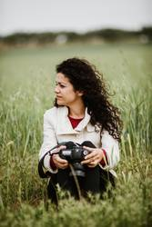 Girl Sitting in fields with a camera