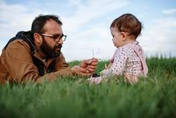 Father showing grasshopper to children