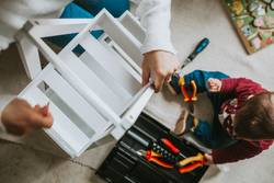 Woman assembling furniture at home with Daughter