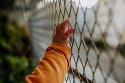 baby hand on fence