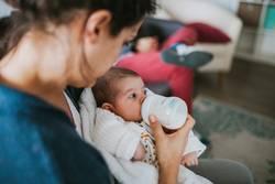 Aunt bottle feeding baby