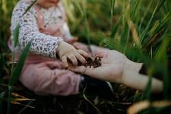 Baby hand touching soil