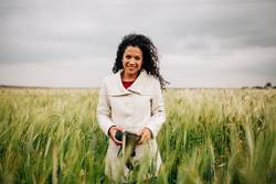 Girl with camera smiling in fields