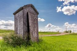 Old wooden outhouse on the prairie countryside in Canada