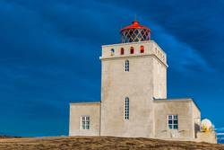 The Dyrholaey lighthouse in Iceland stands guard in stormy skies